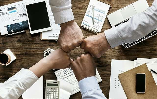 Four hands give a fist bump above a desk covered in business materials