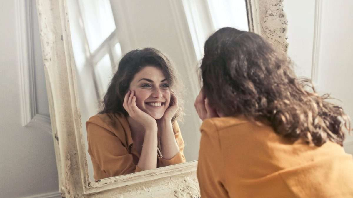 Person leaning close to mirror smiles at their reflection