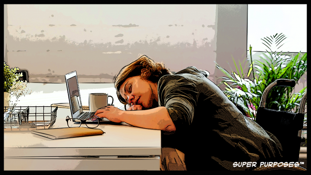 a person sleeping at their computer desk